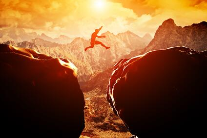 Man jumping between two high cliffs shows the idea that getting good results in ROAS, ROI and Predictive Analytics isn't easy. But advertising effectiveness measurement can make it much more so.